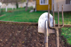 Pitchfork and shovel lying on the fence in the village against the backdrop of a country house and garden in the summer Stock Images
