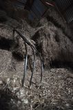 Pitchfork. A three pronged pitchfork resting against stacked and loosened bales of hay at horse stables Stock Images