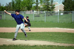 Pitching. A young boy playing pitcher on a baseball team Royalty Free Stock Photos