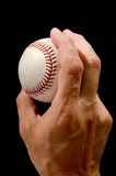 Pitching grip. Man's hand holding a baseball in a pitching grip against black background Royalty Free Stock Photography