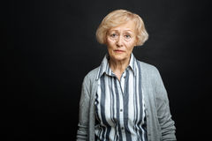Pitiful aging woman demonstrating comparison indoors. Full of frustration. Upset compassionate retired woman expressing sadness while standing against black stock photo