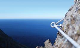Piton del ferro in una roccia del granito con la corda immagini stock libere da diritti