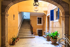 Pitoresque courtyard. In meditteranean city Palma de Mallorca, with yellow walls, stairs and blue window shades Royalty Free Stock Photo