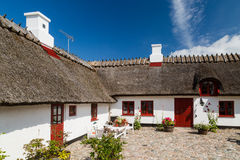Pitoresque farm house. White farm house on sunny day Stock Images