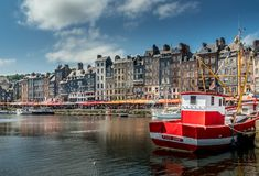 The pitoresque harbour of Honfleur, France. Red boat in front of the pitiresque buildings in Honfleur, Normandy Royalty Free Stock Photo