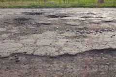 Pits and potholes on asphalt road stock photography