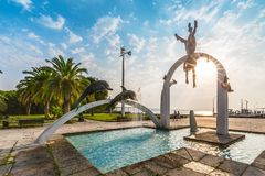 PITSUNDA, ABKHAZIA, SEPTEMBER 23, 2017: Famous sculptural composition `The Sea`, which depicts pearl divers and dolphins, in Pits. Unda in the rays of the rising Stock Photos