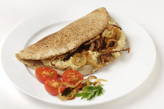 Pitta bread with hommos and onions. A pitta bread, or kubz, sandwich made with hummus and caramelised onions, served with a tomato and parsley garnish Royalty Free Stock Photography