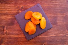 Pitted apricots on slate tray on wood seen from above stock photography