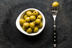 Pitted green olives in bowl. On black table royalty free stock photography
