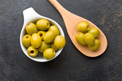 Pitted green olives in bowl. On black table stock photos