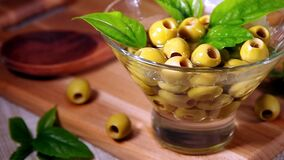 Pitted green olives in a glass cup. Are poured with olive oil stock video footage