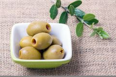 Pitted Green Olives. In a Small Dish with an Olive Branch Stock Images