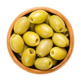 Pitted and marinated green olives in wooden bowl. Fruits of the European olive, Olea europaea. Unripe table olives with yellow to green color. Isolated macro Stock Photography