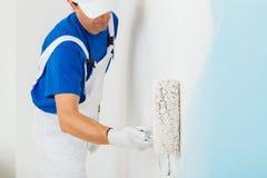 Pittore che dipinge una parete con il rullo di pittura fotografia stock