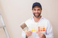 Pittore che tiene un grafico di colore che sorride alla macchina fotografica Fotografie Stock Libere da Diritti