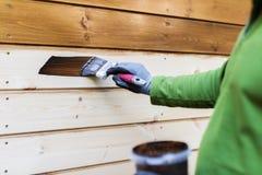 Pittore con il pennello che dipinge la facciata di legno della casa fotografie stock