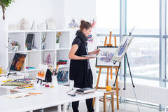 Pittore femminile che assorbe lo studio di arte facendo uso del cavalletto Ritratto di una pittura della giovane donna con le pit Fotografia Stock Libera da Diritti
