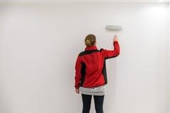 Pittore femminile con il rullo di pittura davanti alla parete come modello Fotografia Stock Libera da Diritti