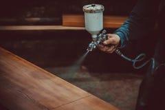 Pittore matrice in una fabbrica - legno industriale della pittura con la pistola a spruzzo Fuoco molle immagine stock