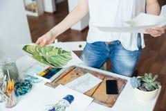 Pittore moderno della donna che esamina i suoi disegni nella classe di arte Fotografie Stock