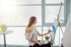 Pittore, vista sul mare europea del disegno della ragazza su tela nella sua officina Concetto delle classi di fine-arte Fotografia Stock