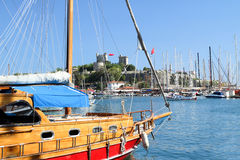 Pittoresk boat in Bodrum harbor with view to famous St. Peter Ca stock image