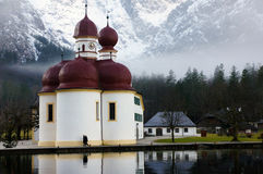 Pittoresk kyrka vid konungs sjö Arkivfoto