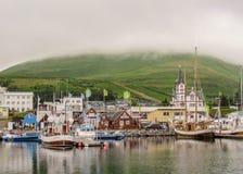 Pittoresk panorama av staden Husavik, färgrika hus och kyrkan reflekterar i havsvattnet, nordliga Island royaltyfria foton