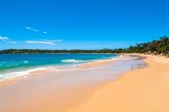 Pittoresk sandstrand med mjuka vågor och blå himmel Arkivbild