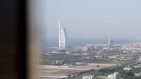 Pittoresk sikt av den Dubai staden och blått från fönstret av ett hotellrum materiel Bedöva sikten av den Burj Al Arab lyxen arkivfilmer