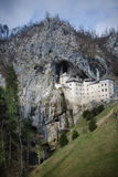 Pittoresk sikt av den Predjama slotten som placeras i mitt av en imponerande klippa i Slovenien Arkivbild
