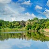 Pittoresk sjö, skog på bankerna och himmel Royaltyfri Foto