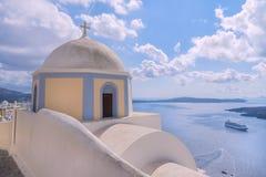 Pittoresk traditionell grekisk kupolformig kyrka på den Santorini ön och härlig panoramautsikt på caldera och vulkan på bakgrund Royaltyfri Foto