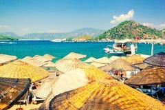 Pittoreska vide- strandparaplyer på den soliga stranden av turkiska riviera arkivbilder