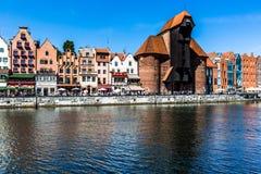 Pittoreskt landskap i den gamla staden av Gdansk i Polen med den Motlawa floden och kranen på det avlägsna slutet Arkivfoton