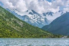 Pittoreskt landskap med snö-korkade bergmaxima och en sjö Royaltyfria Bilder