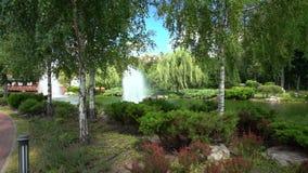 Pittoreskt stads- parkerar och sjön med grönska
