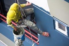Pittori che appendono sul rotolo, colore di verniciatura sulla parete della costruzione Fotografia Stock