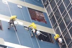 Pittori che appendono sul rotolo, colore di verniciatura sulla parete della costruzione Fotografia Stock Libera da Diritti