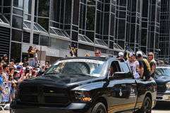 Pittsburgh Penguins Stanley Cup parade. A pick up truck passes the crowd with various employees from the Pittsburgh Penguins organization as the acknowledge the Stock Photos