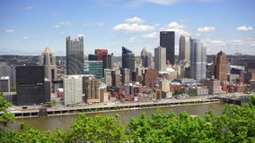 Pittsburgh Pennsylvania Downtown Urban City Skyline Monongahela River. Rush hour traffic rolls by between the river and Pittsburgh PA stock video footage