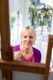 Pittura anziana felice della donna per il divertimento nel paese Immagine Stock Libera da Diritti