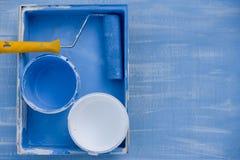 Pittura blu e bianca nella vista superiore delle latte rullo con una maniglia gialla per le pareti di verniciatura fotografia stock libera da diritti