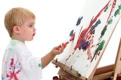Pittura caucasica del ragazzo del bambino al supporto Fotografia Stock