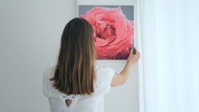 Pittura d'attaccatura della giovane donna sulla parete video d archivio