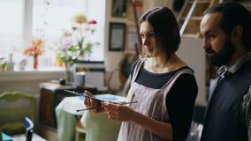 Pittura d'istruzione della giovane donna in uomo esperto dell'artista sul cavalletto allo studio della scuola di arte - la gente  Fotografie Stock