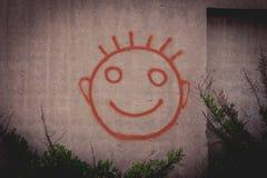 Pittura dei graffiti del fronte sorridente felice rosso su un muro di cemento Fotografia Stock
