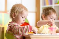 Pittura del bambino con il pennello Fotografia Stock