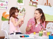 Pittura del bambino con l'insegnante in aula. Fotografia Stock Libera da Diritti